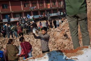 A man takes a selfie at the historic Dharahara Tower, a city landmark, that was damaged in Saturday's earthquake in Kathmandu, Nepal, Monday, April 27, 2015. A strong magnitude earthquake shook Nepal's capital and the densely populated Kathmandu valley on Saturday devastating the region and leaving tens of thousands shell-shocked and sleeping in streets. (AP Photo/Bernat Armangue)